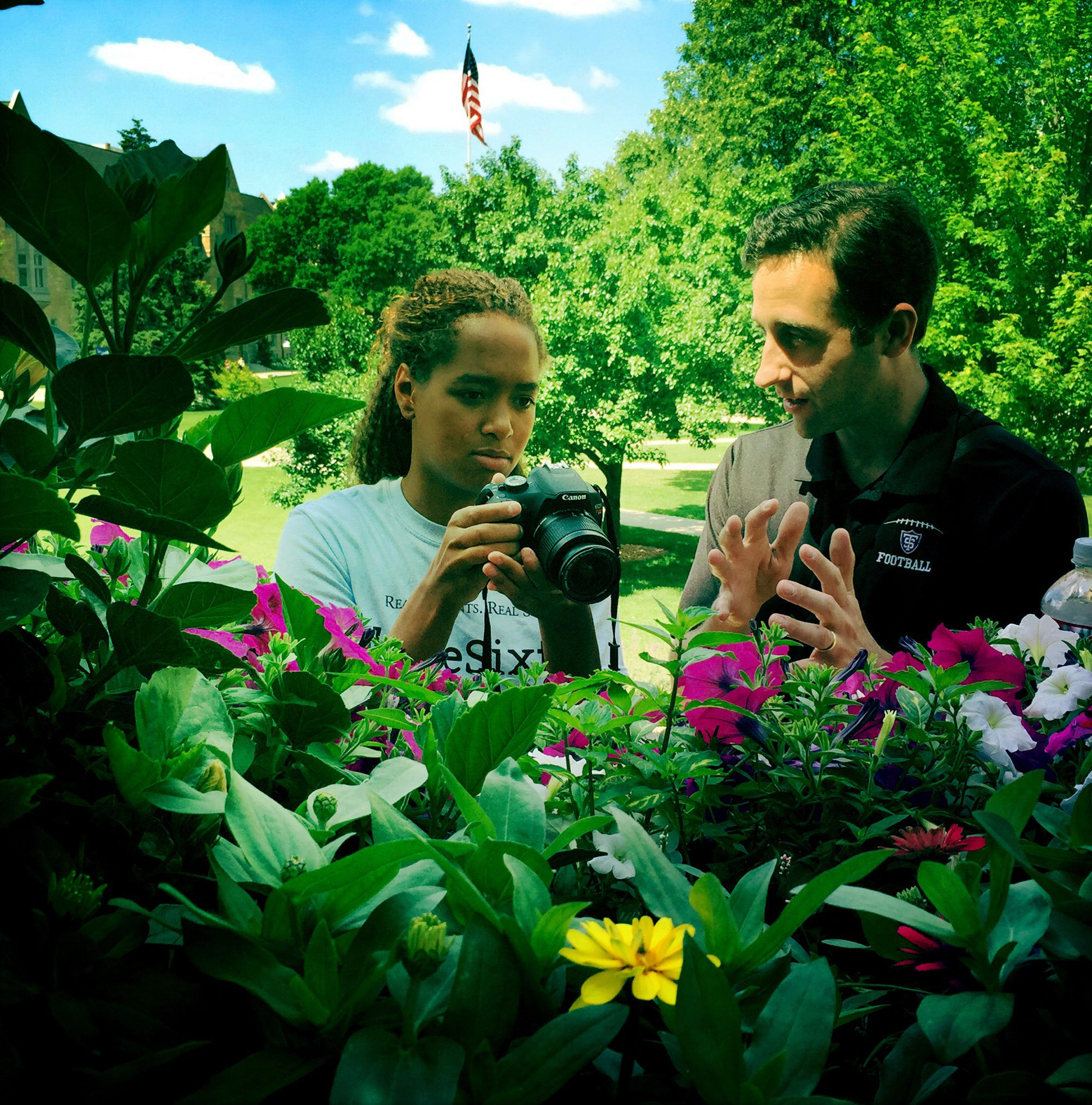 Student taking a photo of flowers with an adult next to her
