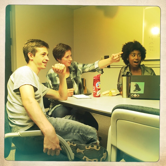 students at a table looking, animatedly, at something off camera