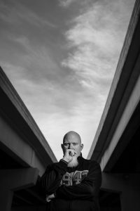 Brother Ali standing underneath two bridges in black and white.