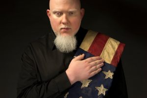 Brother Ali with American flag draped over shoulder and right hand over heart.