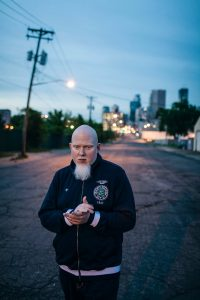 Brother Ali walking in a Minneapolis street at dusk, downtown in the background.