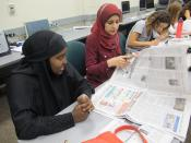 a row of five young women looking over newspapers at a table
