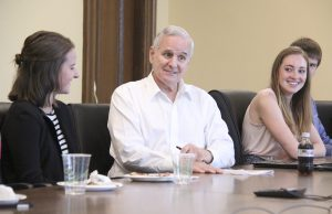 MN Gov. Mark Dayton at a table with young people.