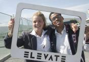 """Emily Doss in Cape Town, South Africa holding up a sign that says, """"Elevate."""""""