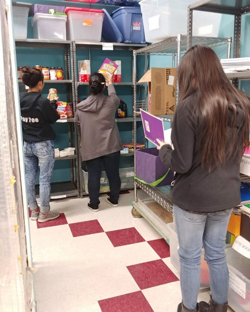 Students from Roseville Area High School in the school's food shelf, the result of a service learning project by students several years ago. (Photo by Shimin Zhang, ThreeSixty Journalism)