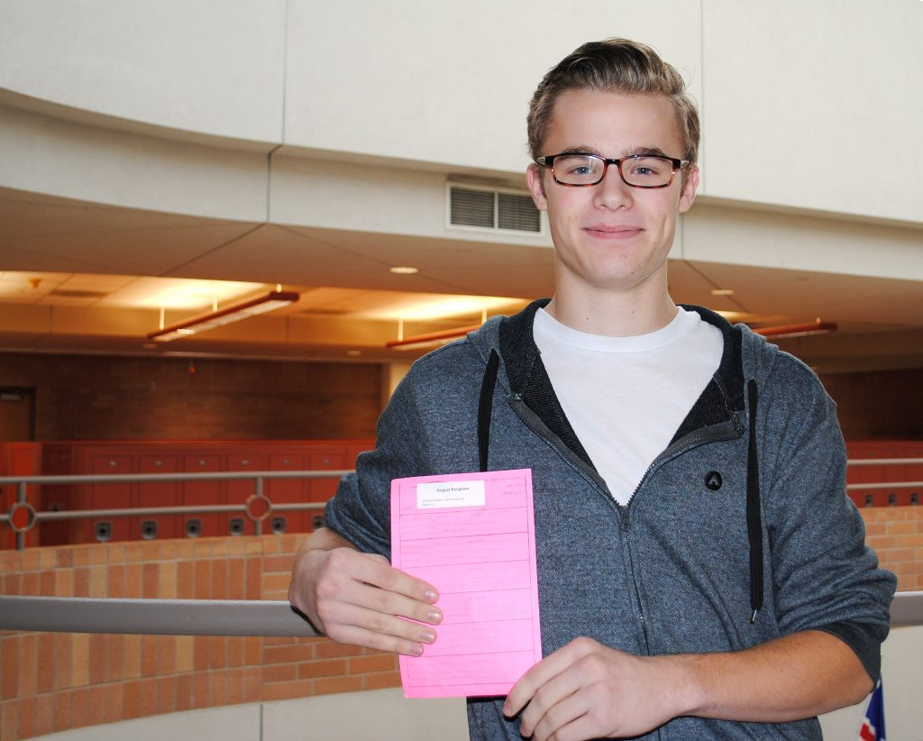 "August Bengtson, a senior at Champlin Park High School, holds up his hall pass, a new system at the high school that limits the number of times students can leave the classroom to 12 per three-month trimester. Bengtson created a social media post in response to student concern, asking students to ""like"" or comment on the post as a sign of support. (Amari Graham/ThreeSixty Journalism)"