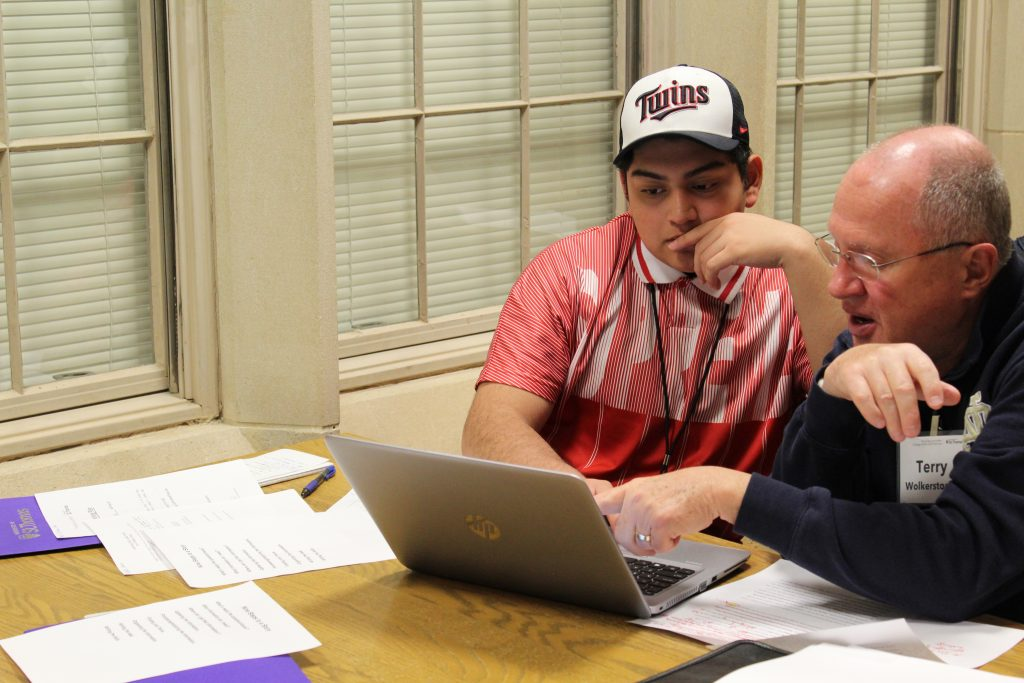 Cristo Rey Jesuit High School student Marco Beltran Galan works with writing coach Terry Wolkerstorfer on his college essay.