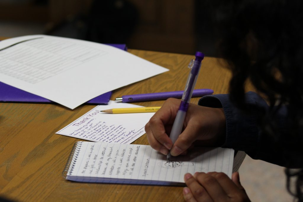 A ThreeSixty student takes notes in her reporter's notebook.