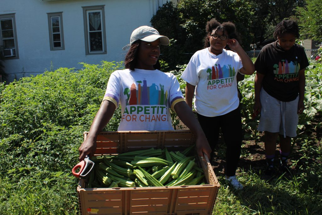 Aaliyah Demry hauls a crate of newly picked okra, while talking to friends Arieana Moore, left, and Omariasha Houston.