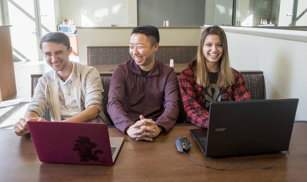 University of League of Legends president Adam Thao (center), club member Lani Dubberstein (right) and gamer Xander Westgaard share a laugh.