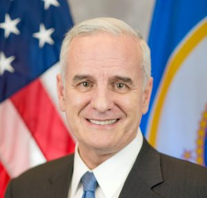 MN Gov. Mark Dayton headshot in front of MN and U.S. flags