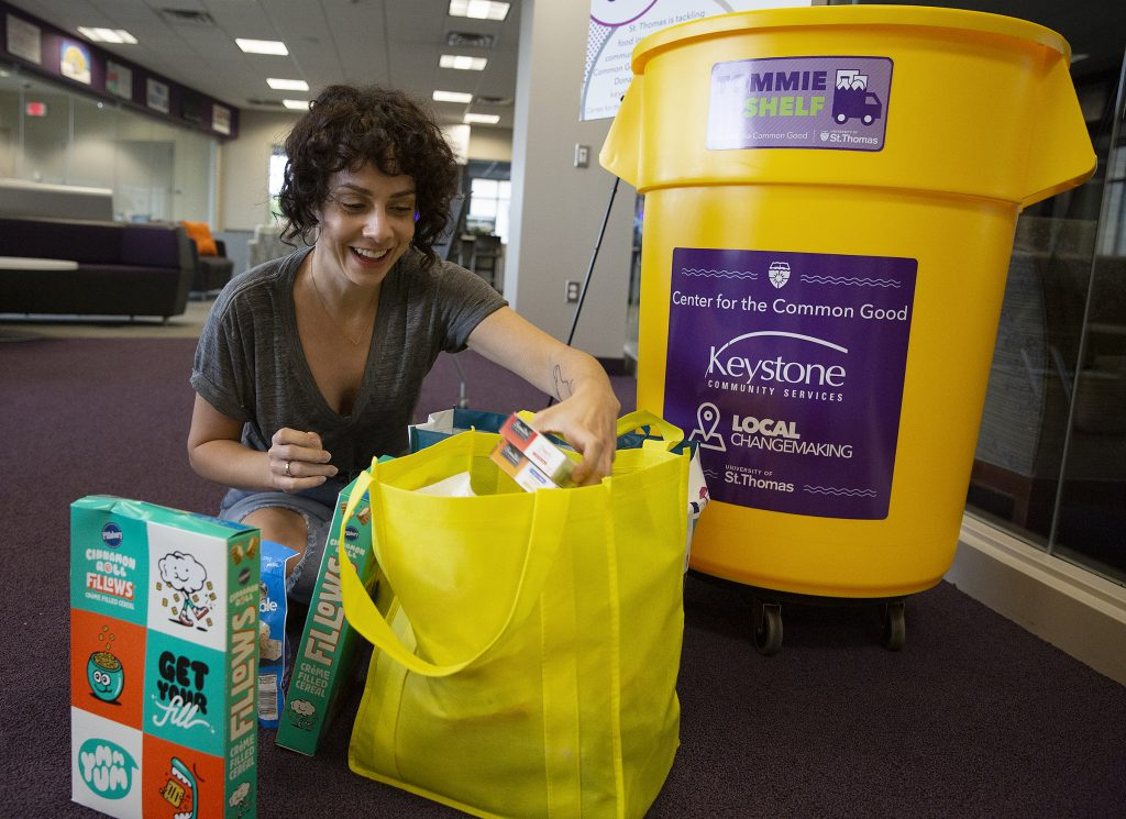 Casey Gordon sorts through donated groceries in front of a yellow Tommie Shelf bin at the University of St. Thomas.