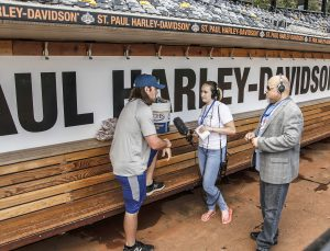 Student standing in front of the St. Paul Harley-Davidson dugout as they interview a subject.