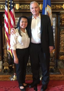 ThreeSixty student Samantha HoangLong and Gov. Mark Dayton stand in front of U.S. and MN flags.