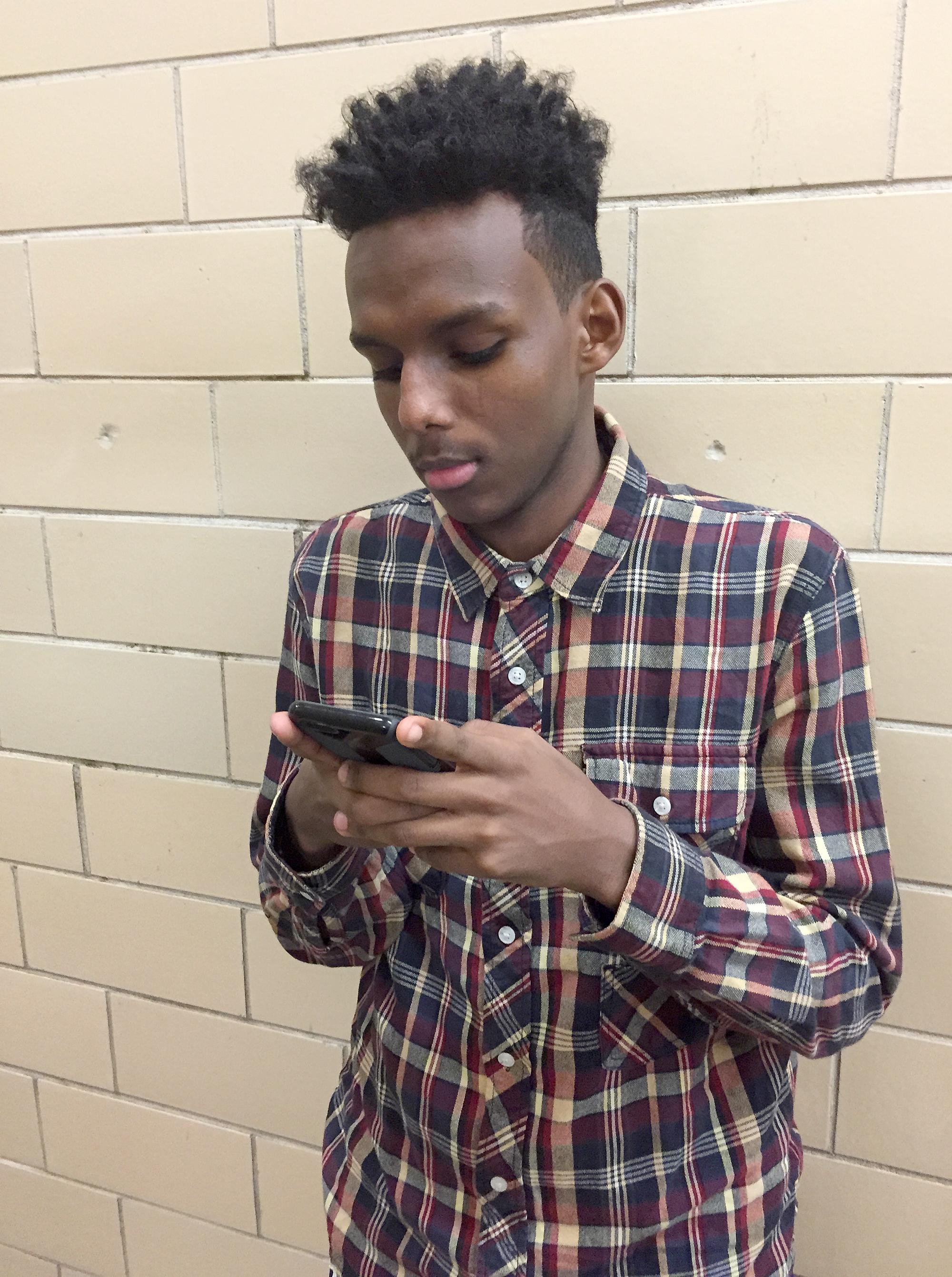 Amir Sharif looking at his phone