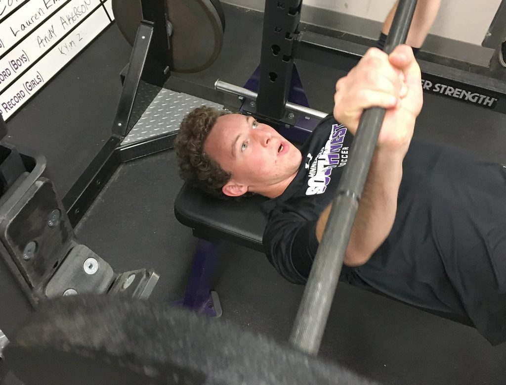 oey Doyle bench-presses during an early morning workout at Minneapolis Southwest High School. Like many high school athletes, Doyle at times struggles to balance the responsibilities of academics and athletics. (Aidan Berg/ThreeSixty Journalism)