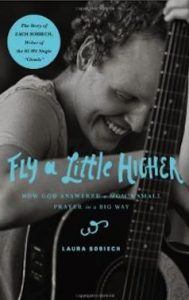 "book cover of ""Fly a Little Higher"", with Zach Sobiech resting leaning his arm and head on a guitar that faces forward"