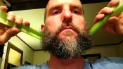 Ben Garvin holding celery pushing each side of his beard forward with celery.